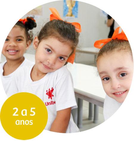 Três meninas sorriem para a câmera, essas usam camiseta com logo vermelho da Unibes e laço laranja no cabelo.