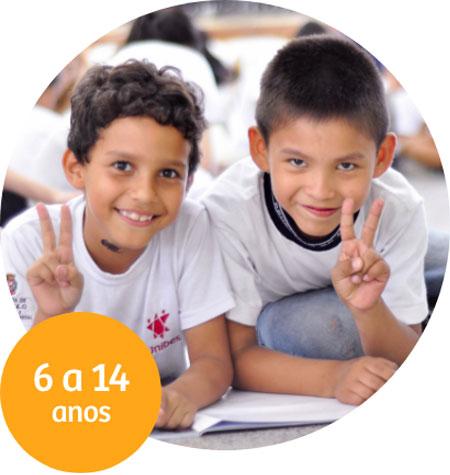 Dois meninos sorriem para a câmera, apoiados em uma mesa fazendo o símbolo de paz e amor com as mãos.