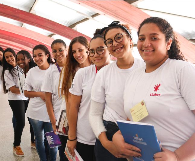 Foto de 8 garotas enfileiradas, todas olham para a câmera sorrindo e segurando material escolar.