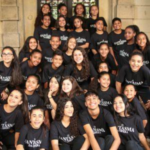 Na imagem de fundo vários jovens sorriem para a câmera, todos com uma camiseta preta escrita Fantasma da Ópera.