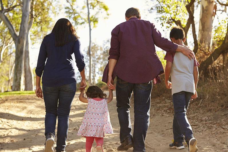 A fotografia é de uma família de costas caminhando em uma estrada de terra, com árvores ao redor. São 4 pessoas representadas, uma mulher, uma criança de 2 anos, um homem e um menino de 8 anos, nessa ordem.