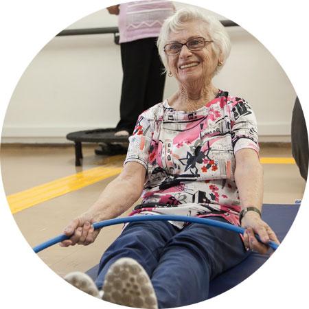 Na foto idosa sorri, sentada com as pernas esticadas, com um bambolê na mão e em cima das pernas.