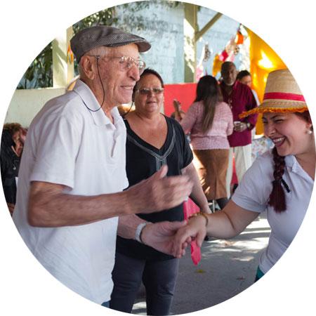 Na foto mulher com chapéu de festa junina sorrindo da a mão para idoso que usa boina e está em movimento.