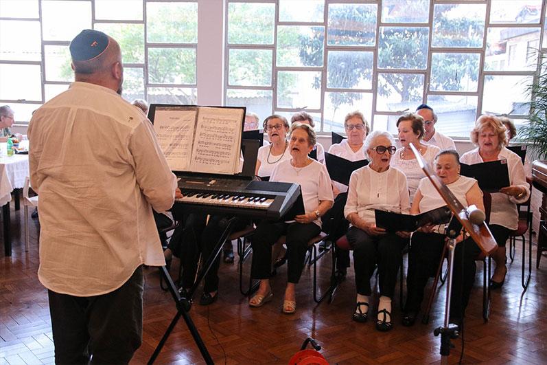 Na imagem um idoso de quipá em frente a um piano conduz uma aula de música e alguns idosos de frente, sentados com um livro aberto cantam.