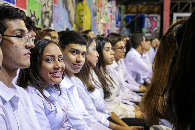 Duas fileiras extensas de jovens sentados de camisa branca olham para frente, dois deles olham para a câmera e sorrindo.