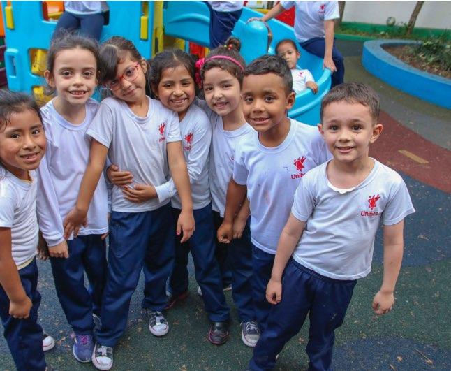 Na foto sete crianças sorriem bem próximas para a foto, todas com o uniforma da Unibes e ao fundo um parquinho.