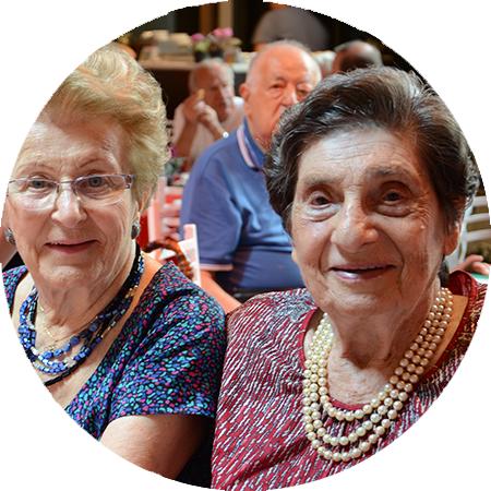 A imagem mostra duas senhoras sentadas olhando para a foto e sorrindo, ambas usam colar de bolinhas. Em segundo plano tem mais idosos sentados em mesas.