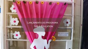 Uma porta de vidro coberta por uma cortina rosa com um recorte de silhueta de mulher colada à ela. No centro da imagem, a frase Lançamento do programa Girls Education