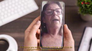 Mão seguram um celular ligado. Na tela do aparelho, uma senhora de óculos.