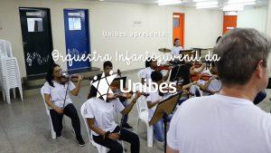 Vê-se por sobre o ombro o maestro da orquestra e os alunos de frente para ele, sentados tocam violino.