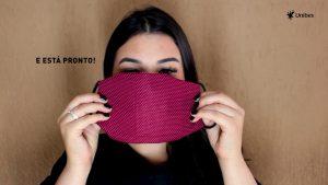 Uma mulher segura em frente ao rosto uma máscara vermelha.
