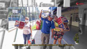 Duas mulheres e um homem carregam cestas básicas nos braços