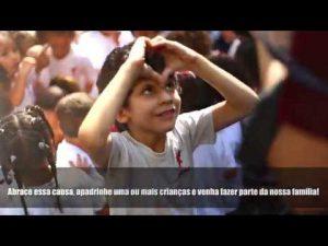Uma criança sorri e faz um coração com as mãos