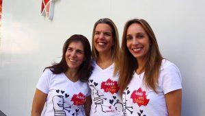 Nicole, Cynthia e Liora, diretoras da Unibes, estão abraçadas. Elas vestem uma camiseta branca. Na camiseta está o logo do programa adote um futuro estampado.