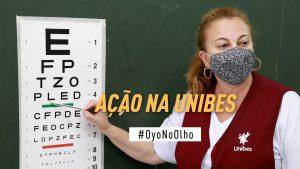 """Professora da Unibes aponta para um quadro com letras de tamanhos diferentes. No centro da imagem está escrito """"ação na Unibes. #Oyonoolho"""""""