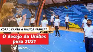 """Na tela está escrito """"Coral Infantojuvenil da Unibes canta a música Pausa. Completo! O desejo da Unibes para 2021"""". Na imagem, a maestrina Kesia rege os alunos, que estão distantes uns dos outros e usam máscara e uniforme da Unibes"""