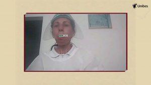 A imagem mostra uma cuidadora dos idosos atendidos pela Unibes, vestida de branco, paramentada com face shield.